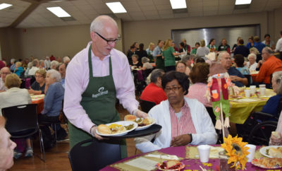 Rob Johnson (left), Board Director of Interfaith of The Woodlands, serves a complete Thanksgiving meal to senior adults at the South County Community Center.