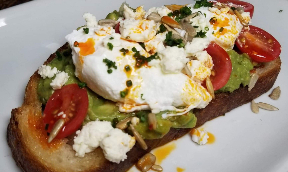 Brunch menu - Avocado Toast - sourdough toast, avocado, feta cheese, cherry tomatoes, aleppo oil, sunflower seeds, two poached eggs. Photo by Nick Rama